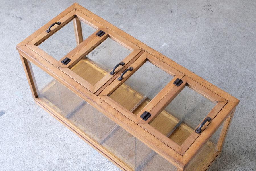 ケース上部に蓋のように扉の付いたガラスショーケース。