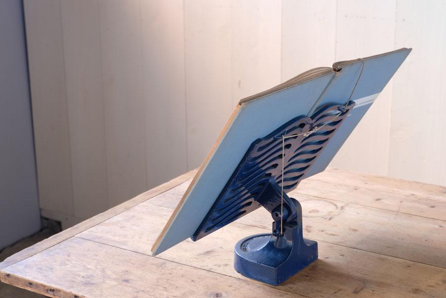 角度調節可能な台の上に楽譜や本を置き、重りの付いた2本の紐でそれを押さえる